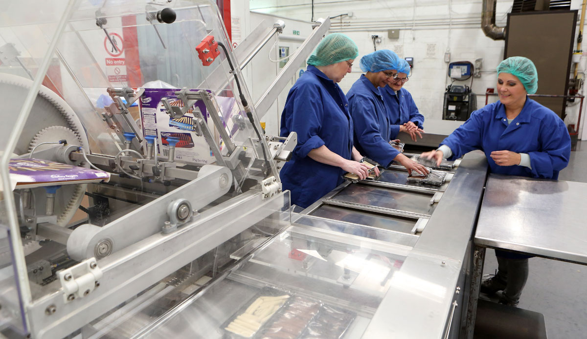 Photo: An automated cartoning machine filling boxes of chocolate truffles