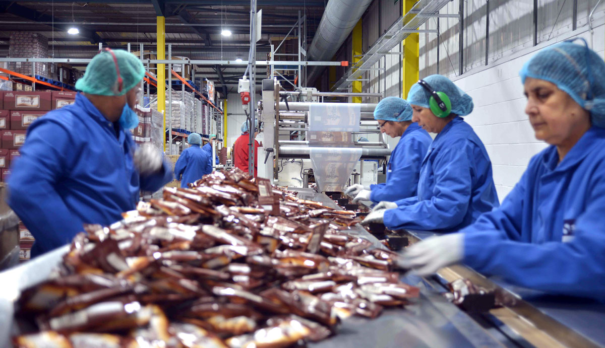 Photo: Workers inspecting confectionery after flow-wrapping at SGL Co-packing factory